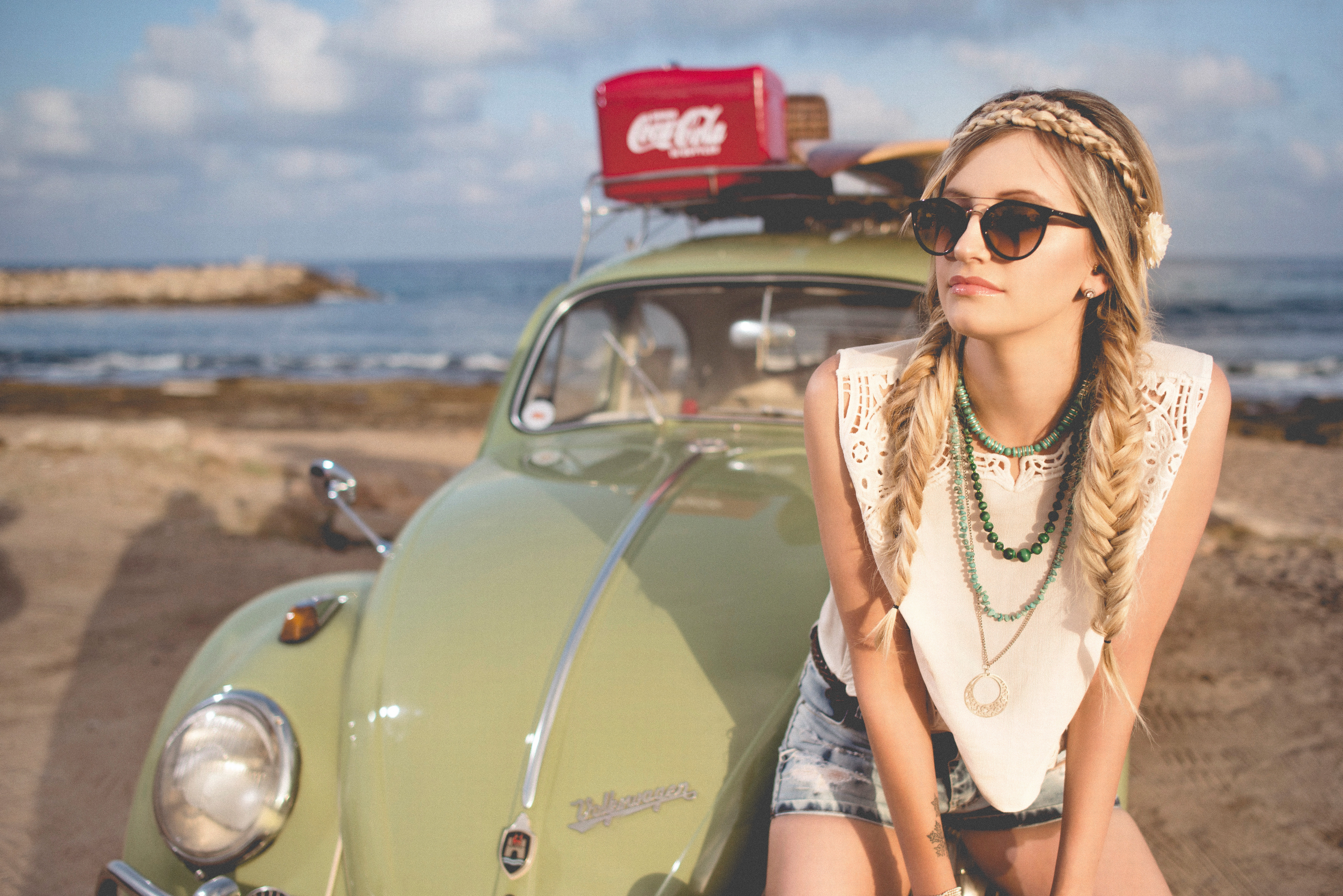 Hipster woman leaning against old VW Beetle that is parked on the beach